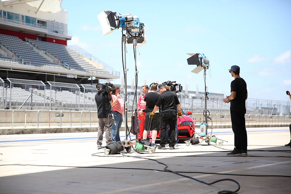 film crew interviewing a race car driver on a racerack